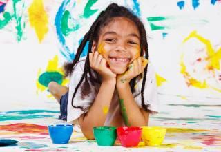 petite fille souriante couchée peinture